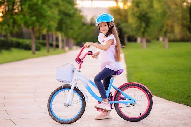 Menina feliz de bicicleta no parque