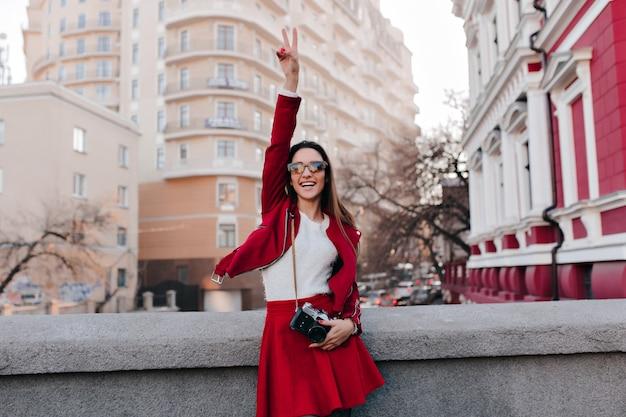 Menina feliz de cabelos escuros curtindo um bom dia durante a sessão de fotos