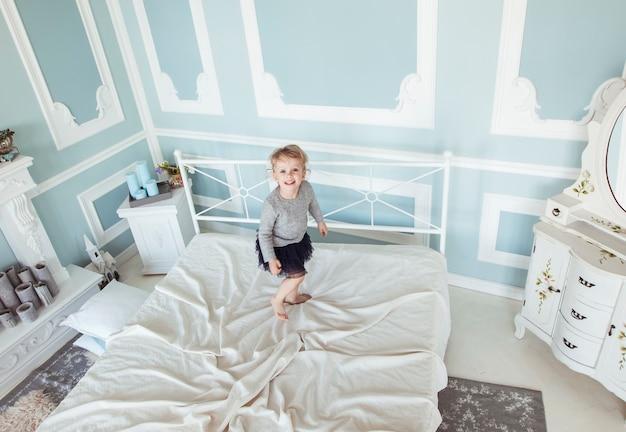 Menina feliz de cinco anos pulando na cama