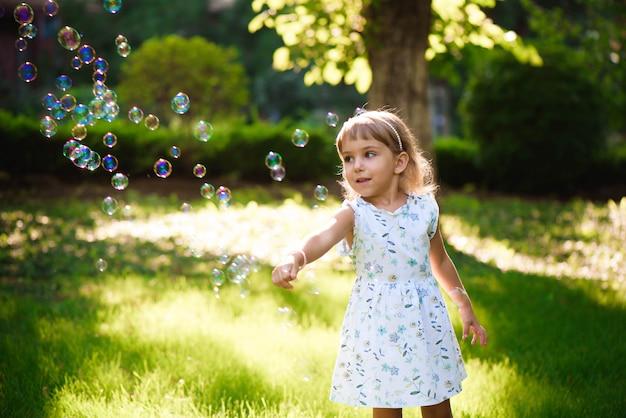 Menina feliz, de pé na grama com dentes de leão