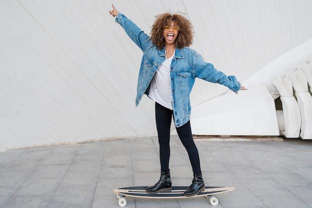 Menina feliz de tiro completo no skate