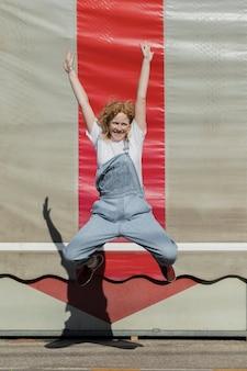 Menina feliz de tiro completo pulando