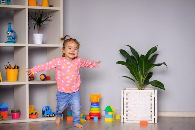 Menina feliz de um ano de idade correndo por aí brincando no jardim de infância, em casa