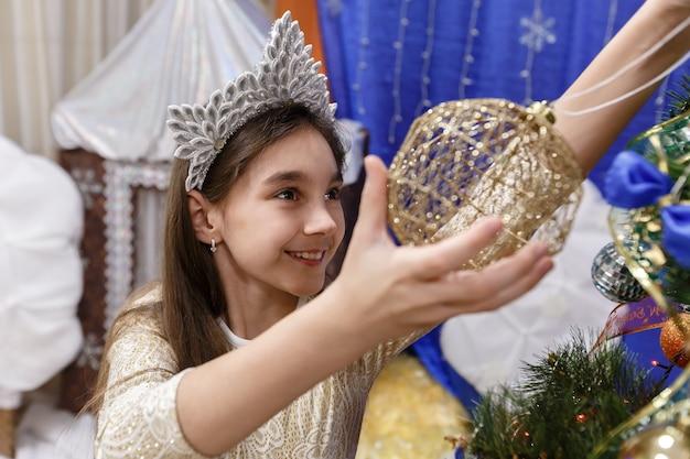 Menina feliz decorando a árvore de natal em casa interior.