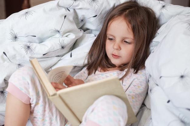 Menina feliz, deitado na cama no cobertor, lendo livro interessante, concentrou a expressão facial