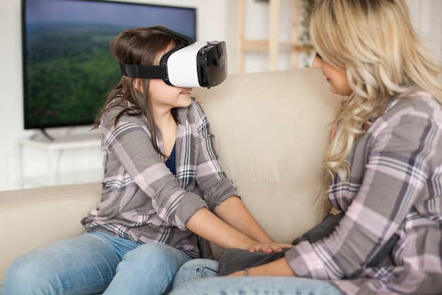 Menina feliz desfrutando de seu fone de ouvido de realidade virtual. jovem mãe.
