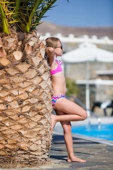 Menina feliz desfrutar de férias perto da piscina