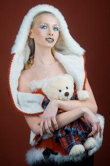 Menina feliz do papai noel segurando o ursinho de pelúcia maquiagem de ano novo natal festa de ano novo feriado