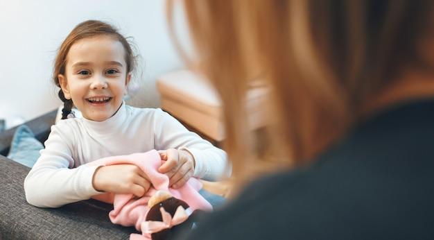 Menina feliz e a mãe brincando com um ursinho de pelúcia na sala