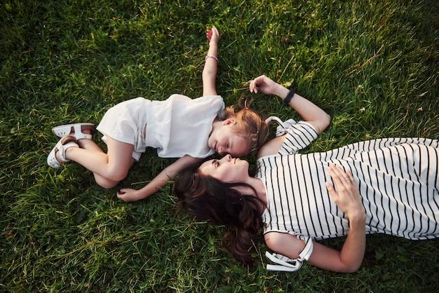 Menina feliz e a mãe dela se divertindo ao ar livre na grama verde em dia de verão ensolarado.
