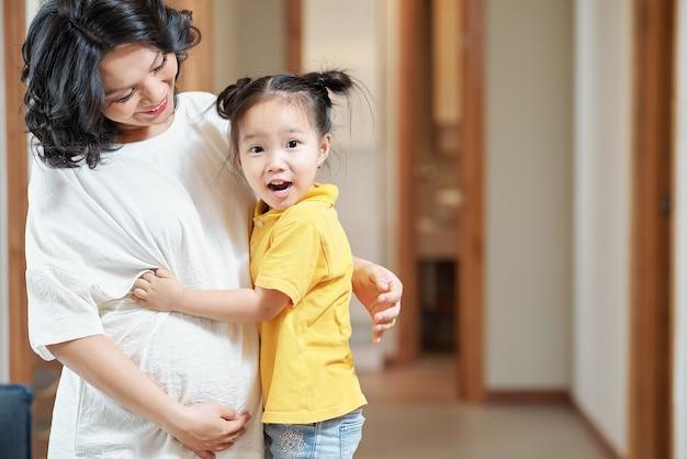 Menina feliz e animada abraçando a mãe grávida e olhando para a câmera