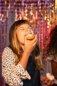 Menina feliz e bonita em uma festa festiva comendo bolinho