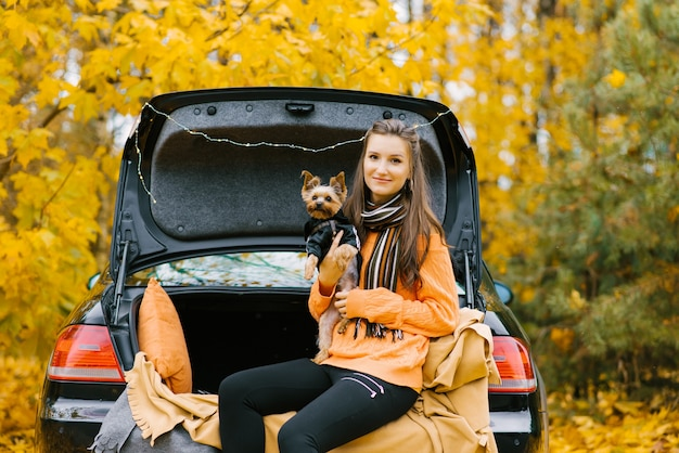 Menina feliz e cachorro sentado no porta-malas de um carro na natureza.