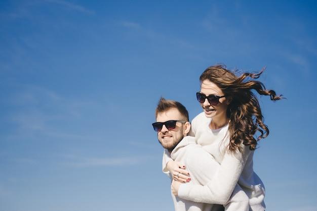 Menina feliz e cara correndo e abraçando em voo contra o céu, viajar conceito de história de amor, foco seletivo