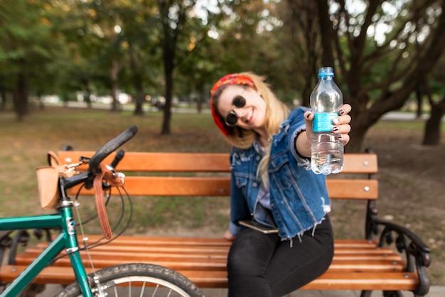 Menina feliz e elegante, sentado num banco de um parque perto de uma bicicleta e mostra uma garrafa de água na câmera.
