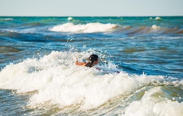 Menina feliz e emocional se banhando nas ondas do mar espumoso e tempestuoso em um dia quente de verão