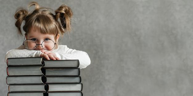 Menina feliz e engraçada de óculos, lendo um livro. garota emocional. para a escola em breve. copie o espaço.