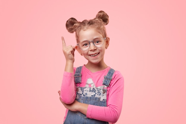 Menina feliz e esperta de macacão jeans e óculos apontando para cima e olhando para a câmera contra um fundo rosa
