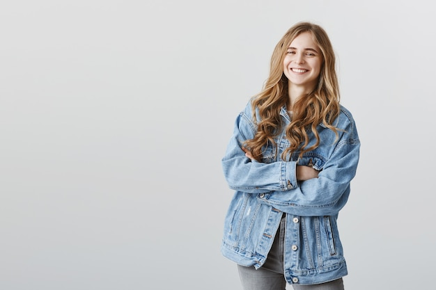Menina feliz e feliz sorridente em jaqueta jeans com os braços cruzados