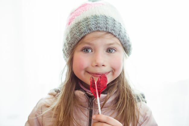 Menina feliz e fofa com pirulito doce com copyspace