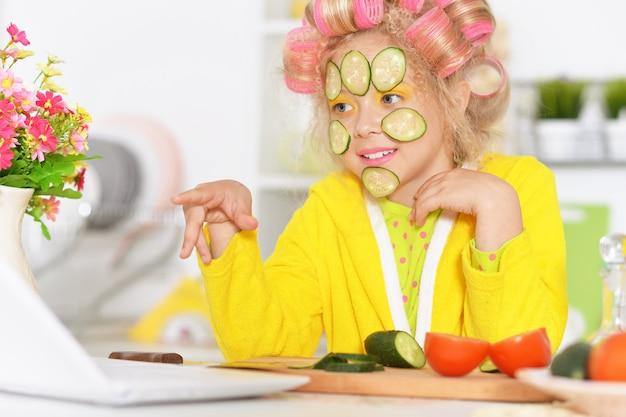 Menina feliz e fofa com rolos de cabelo, laptop e vegetais