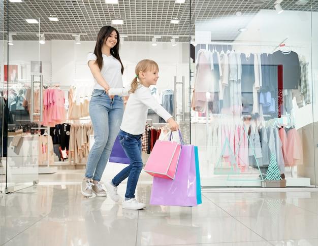 Menina feliz e mãe andando na moderna loja de departamentos.