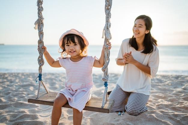 Menina feliz e mãe balançando na praia