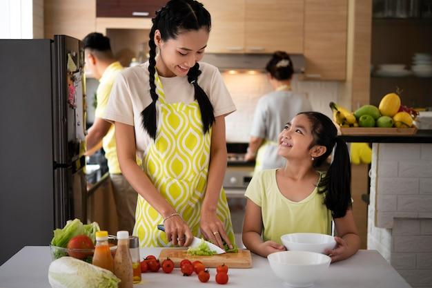 Menina feliz e mãe cozinhando