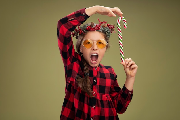 Menina feliz e positiva com uma guirlanda de natal em um vestido xadrez segurando uma bengala de doces e sorrindo alegremente