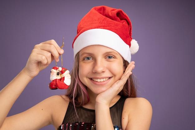 Menina feliz e satisfeita com vestido de festa glitter e chapéu de papai noel segurando brinquedos de natal, olhando para a câmera sorrindo alegremente em pé sobre fundo roxo