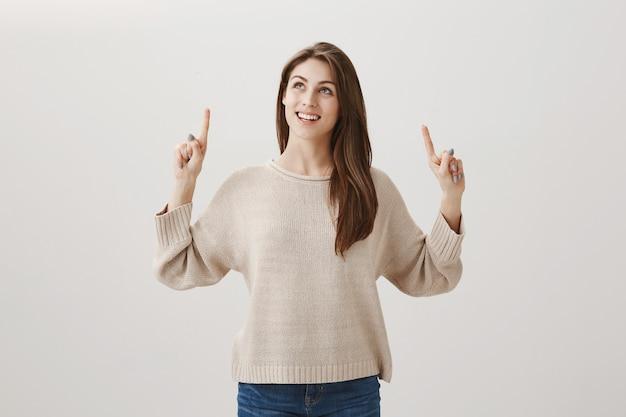 Menina feliz e sonhadora olhando e apontando os dedos para cima