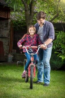 Menina feliz e sorridente aprendendo a andar de bicicleta com o pai no parque