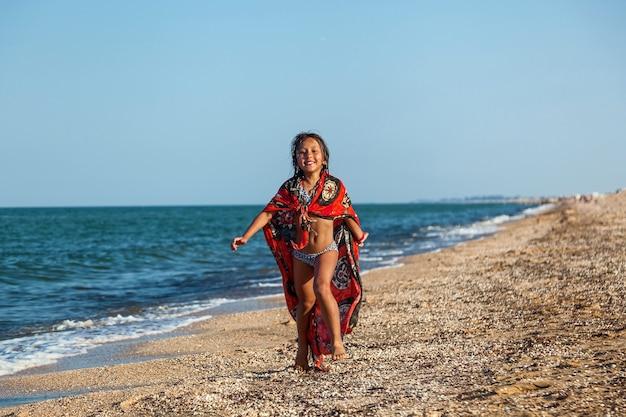 Menina feliz e sorridente brincando com uma bola inflável na praia à beira-mar no verão