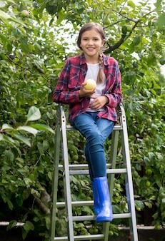 Menina feliz e sorridente colhendo maçãs maduras no jardim em um dia ensolarado