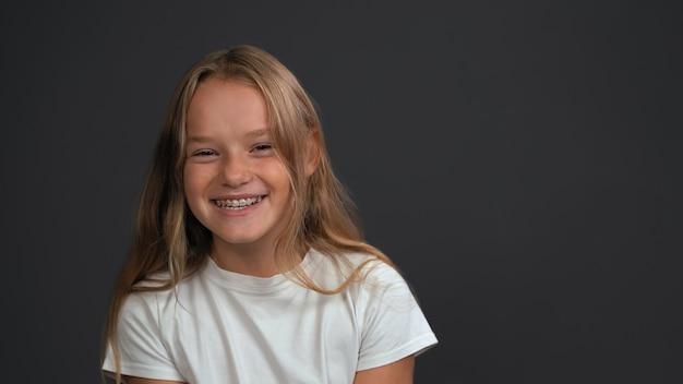 Menina feliz e sorridente com cabelo loiro em pé olhando para a frente usando uma camiseta branca isolada na parede cinza escuro