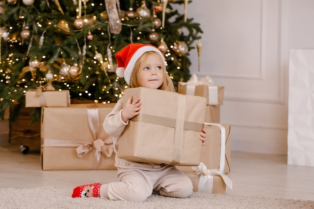 Menina feliz e sorridente com chapéu de papai noel com uma caixa de presente de natal perto da árvore de natal em casa