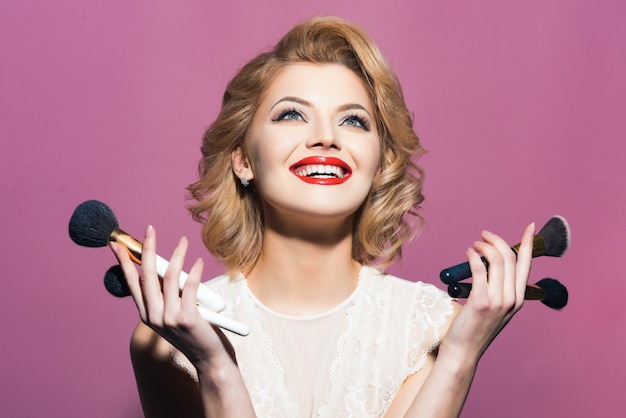 Menina feliz e sorridente com elegantes pincéis de maquiagem de fixação.