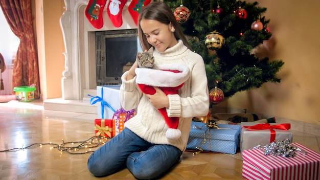 Menina feliz e sorridente com o gato na lareira e a árvore de natal