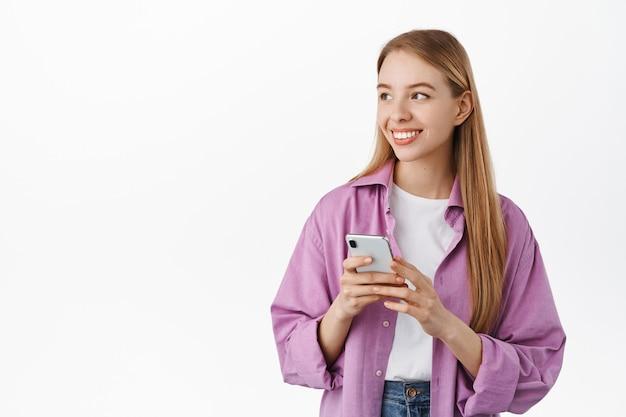 Menina feliz e sorridente com roupas casuais, usando smartphone, segurando o telefone nas mãos e olhando de lado para o logotipo com um rosto alegre e descontraído, em pé sobre uma parede branca