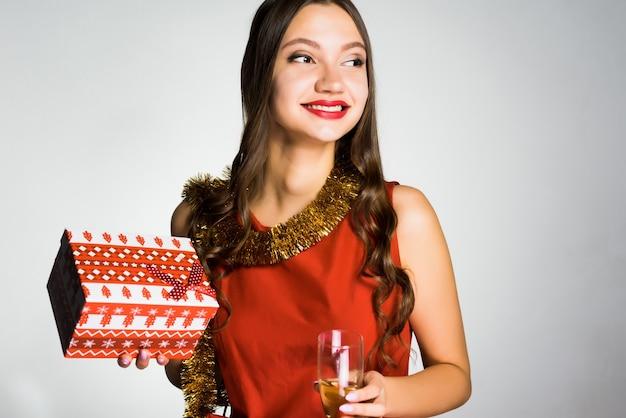 Menina feliz e sorridente com vestido vermelho comemorando o ano novo, segurando um presente e uma taça de champanhe