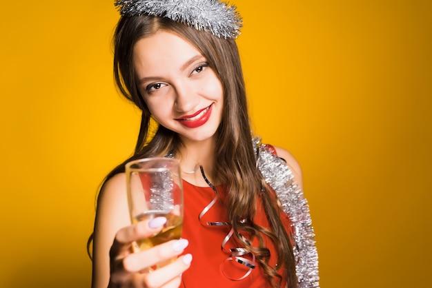 Menina feliz e sorridente com vestido vermelho comemorando o ano novo, segurando uma taça de champanhe