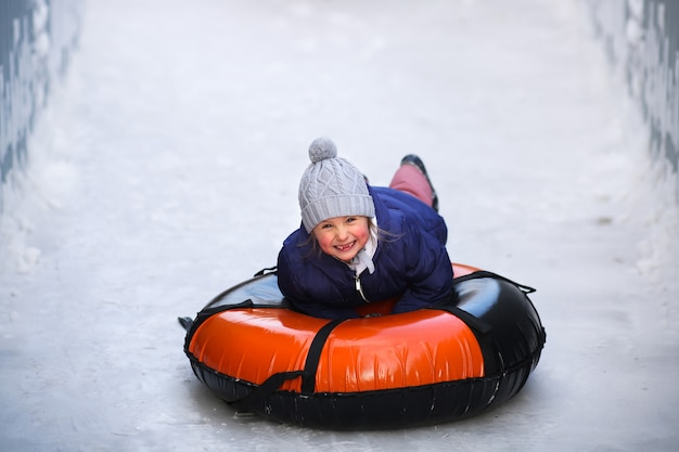 Menina feliz e sorridente deslizar para baixo da lâmina de gelo, senta-se em um tubo inflável.