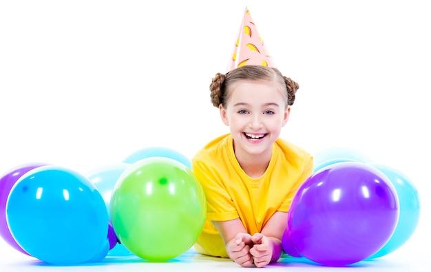 Menina feliz e sorridente em t-shirt amarela deitada no chão com balões coloridos - isolados em um branco.