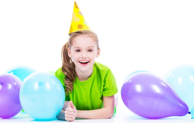 Menina feliz e sorridente em t-shirt verde deitada no chão com balões coloridos - isolados em um branco.