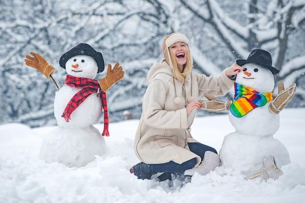 Menina feliz e sorridente fazendo boneco de neve em um dia ensolarado de inverno