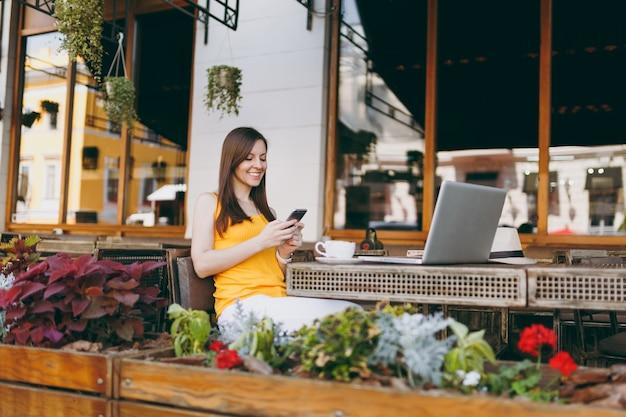 Menina feliz e sorridente na rua ao ar livre, café, café, sentado à mesa com o computador laptop pc, mensagem de texto no amigo do celular, no restaurante durante o tempo livre