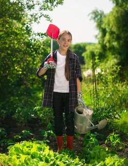 Menina feliz e sorridente posando no jardim com pá e regador