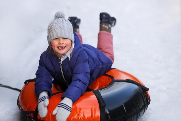 Menina feliz e sorridente se senta em um tubo inflável.
