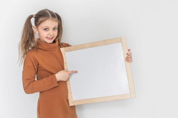 Menina feliz e sorridente segura uma prancheta vazia, aponta a direção com o dedo indicador. copie o espaço para teste em fundo branco