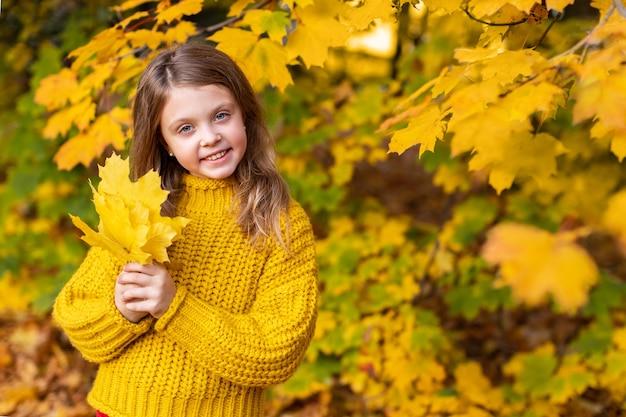 Menina feliz e sorridente segurando nas mãos as folhas de bordo amarelo no parque outono ao ar livre. copie o espaço para o texto